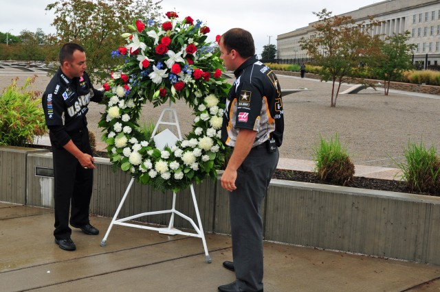 "Army Top Fuel driver Tony ""The Sarge"" Schumacher (left) and Army NASCAR driver Ryan Newman place a wreath in memory of Lt. Gen. Timothy J. Maude at the Pentagon Memorial Sept. 8, 2011. Maude, who was killed in the Sept. 11, 2001 attack on the Pentagon, had been instrumental in sponsoring the NHRA and NASCAR to represent the Army."