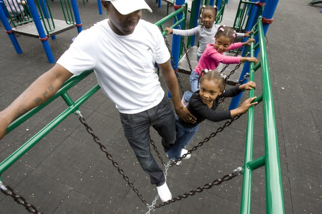 Dee McNeil  walks with daughters Mya , 4,  Jayda , 5, and Janiah , 6 , across a chain bridge while spending a little leisure time playing at the the Summer Cove playgrounds on September 9, 2011 at JBLM. Dee's a stay at home father while his wife is serving overseas and won't be home until next April.