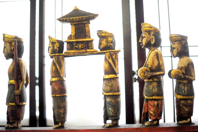A grouping of wooden figures from Thailand was found covered in mud at a yard sale in Seattle. It decorates the seating area at the JBLM language center.