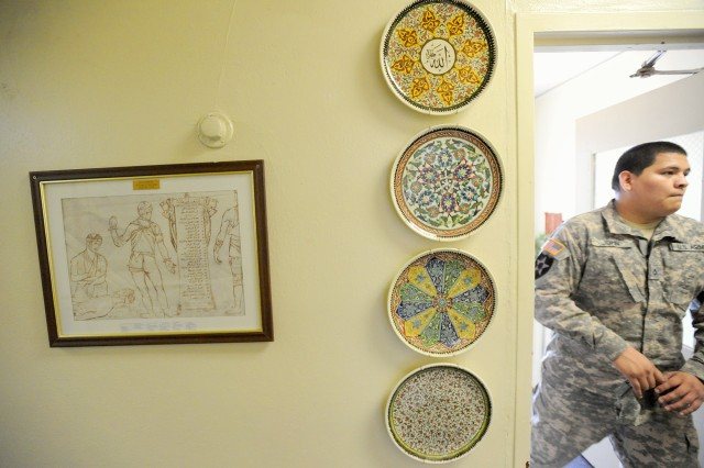 An Iraqi bandage, donated by retiree William Gayton, hangs next to a set of plates at the JBLM language center.