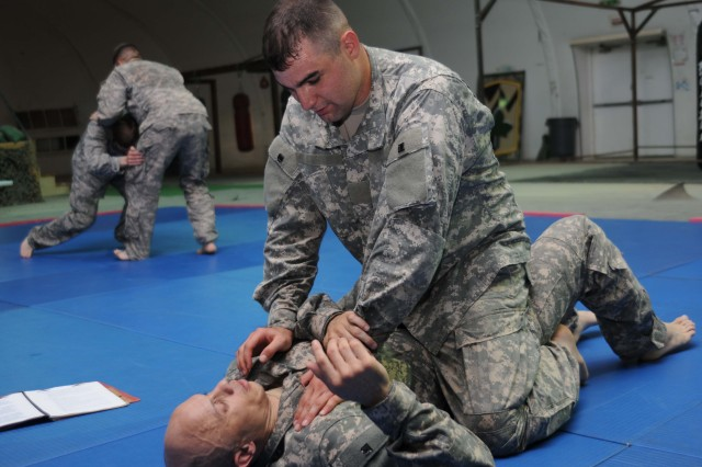 (Top to bottom) Pfc. Jeremy Rivera, 29th Combat Aviation Brigade, and Sgt. Tomes Weekes, 8th Ordinance Battalion, practice combatives drills on Contingency Operating Base Adder, Sept. 1.