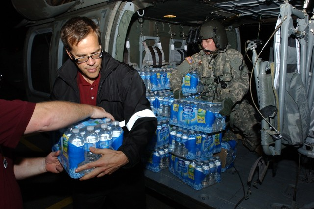 BINGHAMTON, N.Y.- New York Army National Guard Spc. Kyle Monroe  arranges packs of water bottles on a NY National Guard UH-60 helicopter that landed at The State University of New York,Binghamton on Thursday night to pick up supplies headed for a shelter in the Town of Nichols. Residents were cut off from regular vehicle traffic because of flood waters.