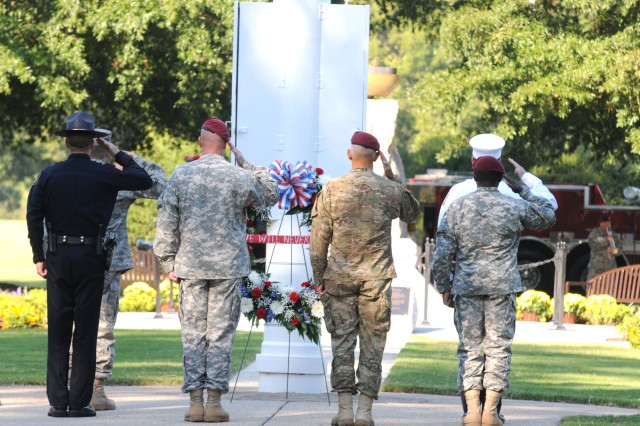 From left to right, Calvin Prouty, Fort Bragg deputy provost marshal, Command Sgt. Maj. Todd Spradling, 16th MP Brigade, Maj. Gen. James L. Huggins, 82nd Airborne Divison and Sgt. 1st Class Shawndell A. Rouse, 82nd Abn. Div., place a wreath near Fort Bragg's eternal flame Sunday in remembrance of those who lost their lives during the Sept. 11, 2001 attacks.