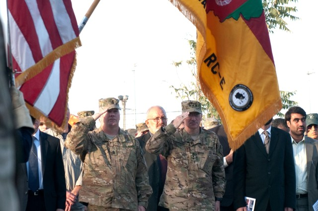 Lt. Gen. Curtis Scaparrotti (center) and Command Sgt. Maj. John Troxell (left), the commander and command sergeant major of ISAF Joint Command respectively, salute the colors during a ceremony in Bagram remembering the attacks of 9/11. A steel remnant from Ground Zero stands tall among NATO flags to serve as a constant reminder to all those that visit the Regional Command East headquarters.