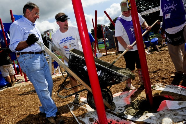 Defense Secretary Leon E. Panetta pours concrete into a playground's foundation during the 9/11 National Day of Service on Fort George G. Meade, Md., Sept. 10, 2011.