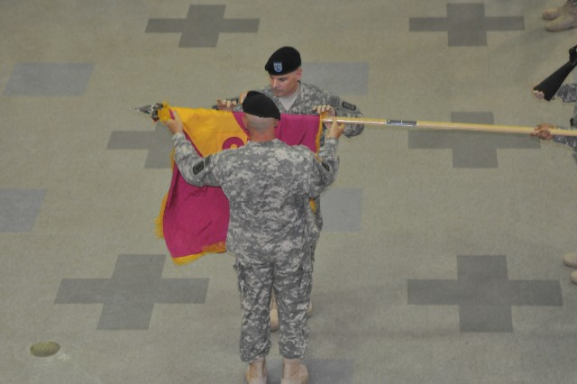 Colonel Thomas J. Langowski, outgoing commander of 52nd Ordnance Group (EOD) uncases the colors with the help of Command Sgt. Maj. Robert Hockstedler, 52nd Ordnance Group Sept. 1, during the change of command ceremony at the Passenger Processing Center at Campbell Army Airfield. Col. Marue R. Quick was introduced at the ceremony as the 52nd's new commander. Photo by Glen Paddie, Fort Campbell Courier staff.