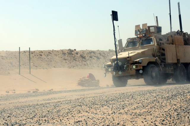 A mine-resistant, ambush-protected vehicle drives on a road located near one of the many motor pools staged here in anticipation of the repositioning of service members, civilians and equipment from Iraq. The redistribution property accountability team, or RPAT, here is prepared to clear up any lingering vehicular issues standing between personnel and their return home.