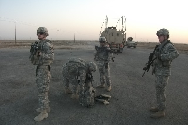 "BASRAH, Iraq "" Soldiers from Blue Platoon, C Company, 1st Battalion, 12th Cavalry Regiment, 3rd Advise and Assist Brigade, 1st Cavalry Division provide security while Spc. Fue Vang prepares an unmanned aerial vehicle for takeoff in Basrah, Iraq, August 15."