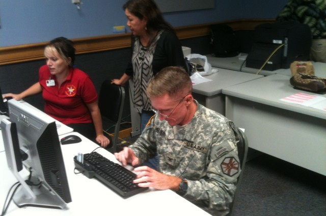 """Col. Douglas Mulbury (right), commander, USAG-Hawaii, responds to a query posted during the USAG-Hawaii Facebook town hall, Aug. 31, 2011, while Lacey Justinger (left), Public Affairs Office, and Gayle Yanagida, Plans, Analysis, and Integration Office, monitor the """"Discussion Board"""" for new topics."""