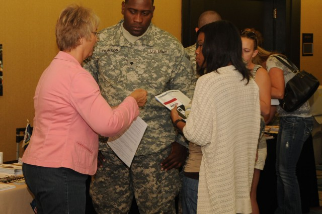 Spec. Delano Howson, a medic with F Co., 5/159th Aviation Regiment MEDEVAC, and his fiancee Sharnelle Jones talk with Marlene Ware, a financial stability educator with Warrior Support Services during a break at the unit's pre-deployment Yellow Ribbon event in Tampa, FL on Spetember 3, 2011. Photo by SFC Joel Quebec, 81st RSC