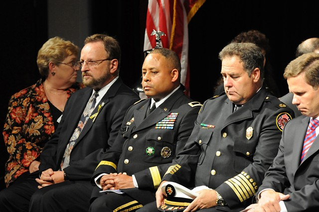 (Left to right) Mr. Wayne Messmer, Brig. Gen. Gracus Dunn, Fire Chief Terrence Vavra, and Congressman Robert Dold reflect during an invocation given at The Buffalo Grove 9/11 10 year Commemorative event at Buffalo Grove high school, Sep 11. U.S. Army photo by Sgt. Carrie Castillo, 85th Support Command Public Affairs Office.
