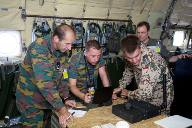 Warrant Officer Thierri Wuillaume and Warrant Officer Chrisophe Theatre, with the Belgian Air Force, load targeting data from a Belgian system into a system used by the German Air Force Sept. 11, 2011, during Bold Quest 2011 being held at Camp Atterbury Joint Maneuver Training Center. Bold Quest 2011 is a NATO exercise to test the interoperability of target identification systems of member nations to reduce friendly fire incidents
