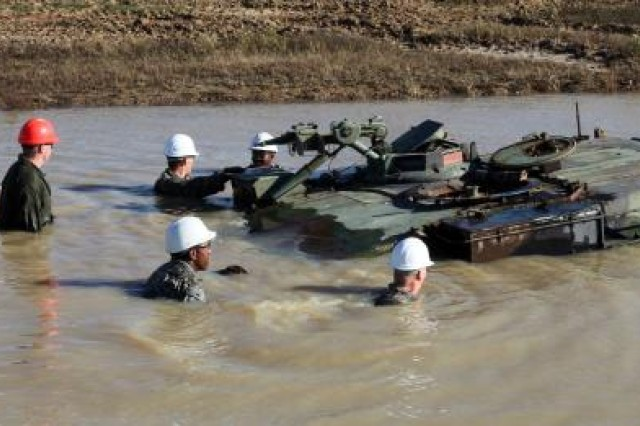 As part of their training, Vehicle Recovery Course students wade through water to assess a M1 tank stuck in a mire pit. These state-of-the art training facilities were constructed as part of BRAC initiatives.