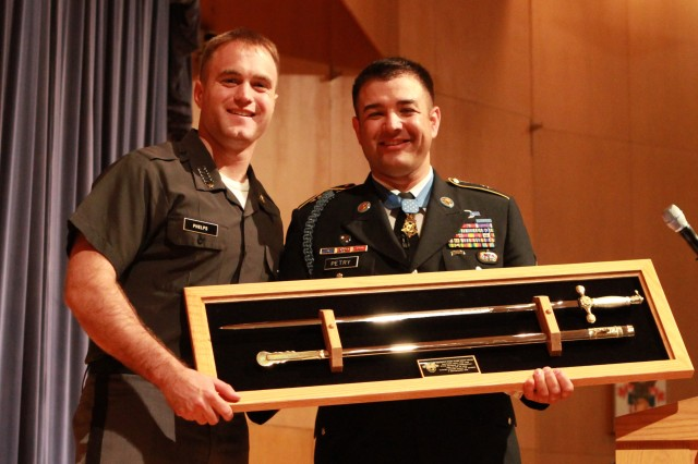 """First Captain Charles Phelps presents a saber to Sgt. 1st Class Leroy Petry following the Medal of Honor recipient's address to the Class of 2012 at Robinson Auditorium. Afterward, Petry videotaped a """"Go Army, Beat Navy"""" Spirit Video with the cadets."""