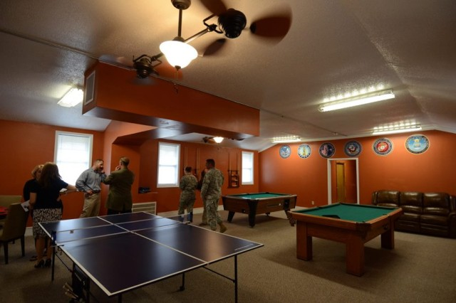 """A group of Soldiers and civilians walk through the """"USO in a Box,"""" which was officially opened at McCrady Training Center after a ribbon-cutting ceremony Wednesday. The facility offers a variety of entertainment activities, such as video games and pool, to the service members assigned there."""