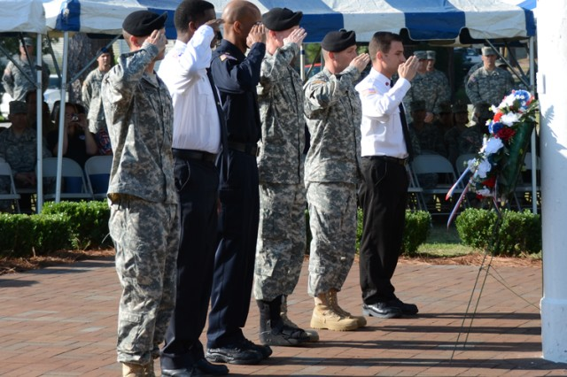 Sgt. Matthew Thornton, Fort Jackson's Soldier of the Year, Theodore Byrd, chief of emergency medical services, Barry Wall, DA police supervisor, Maj. Gen. James Milano, Fort Jackson's commanding general, Post Command Sgt. Maj. Brian Stall and Gino Sita, fire inspector, salute after placing the wreath during a wreath-laying ceremony Friday in front of Post Headquarters. The wreath laying was part of a ceremony commemorating the 10th anniversary of the 9/11 terrorist attacks.