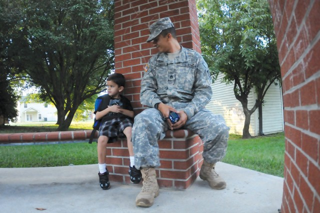 Father-to-son:  Zane gets a final brief from father, Staff Sgt. Jose M. Flores, before his bus arrives.