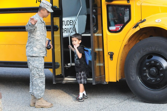 """Zane Daniel moves toward the bus with a bit of trepidation as his father encourages him to say """"goodbye"""" to the family."""