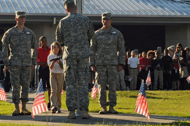Heather Beers, 10, and Savion Price, 10, fifth-graders at Lyman Hall Elementary School in Hinesville, Ga., carry the American and Georgia state flags as part of their duties on color guard with cavalry scouts assigned to Troop A, 6th Squadron, 8th Cav. Regt, 4th IBCT, 3rd ID. Private First Class Jason A. Rose, a Lombard, Ill. native; Staff Sgt. Zachery R. Hagensen, a Twin Valley, Minn. native; and Spc. Catlin T. Eagleman, a Poplar, Mont. native, helped the students raise the flags to half-staff during a ceremony preceding the school's annual America Supports You Freedom Walk held at the school, Sept. 9.