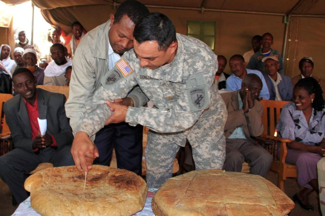 Maj. Antonio Gonzalez, 490th Civil Affairs team chief, and Negele, Ethiopia, Mayor Ato Tesfaye Eyane conduct a bread cutting ceremony as part of the Negele Bridge dedication ceremony Aug. 22, 2011.