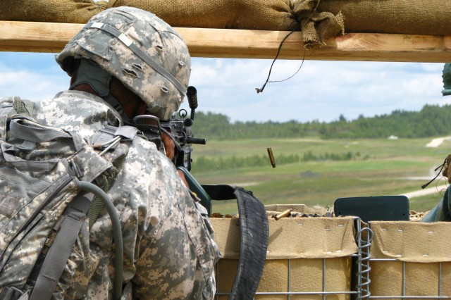 Spc. Sean Vincent, a native of Gretna, La. and a unit supply specialist with the 574th Quartermaster Support Company, 18th Combat Sustainment Support Battalion, fires his automatic weapon during the 574th QMSC platoon defense training exercise June 23 in Grafenwoehr, Germany.