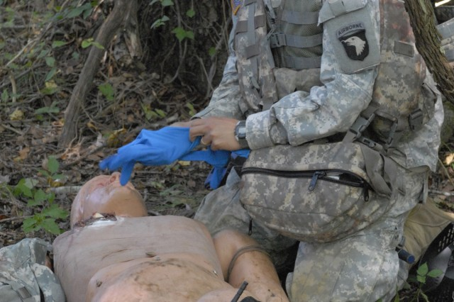 Sergeant Brian P. Baker from B Troop, 175th Cavalry Regiment, 2nd Brigade Combat Team, puts on a pair of latex gloves before providing first aid to a simulated casualty during the 101st Airborne Division Best Medic Competition, Sept. 8-9. Baker placed first in the competition to advance to the Armywide Best Medic Competition. Photo by Spc. Alan Graziano, 101st Airboen Division Public Affairs.