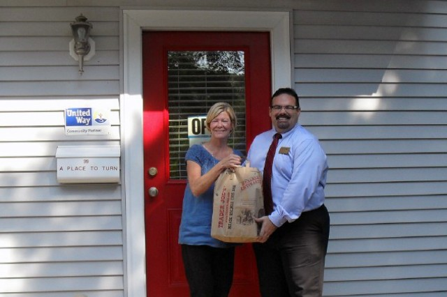 Kent Brickman, Army Community Service director at Natick Soldier Systems Center, delivers more than 200 pounds of nonperishable food and other items to Joanne Barry of A Place to Turn in Natick.