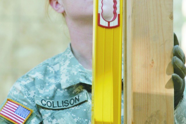 Sgt. Kristen Collison uses a level to make sure a beam is straight.