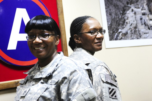 CAMP ARIFJAN, Kuwait - Sgt. 1st Class Wanda (left) and Sgt. 1st Class Yolanda (right) Scott, natives of Rochester, N.Y. are happy to have a family member with them during deployments. The identical twin sisters joined the Army two days apart and have spent most of their 18-year military career on the same post. Yolanda is a minute older and they refer to each other as the youngest and the oldest, as opposed to twins.
