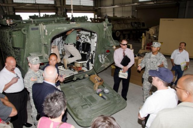Industry reps hear about NIE Drew Hamilton 1st Sgt. Ramon Manzano (center right) with the 2nd Brigade 1st Armored Division, talks to industry representatives about the Soldiers technology needs while on a tour of PEO-I facilities at Fort Bliss, Texas.
