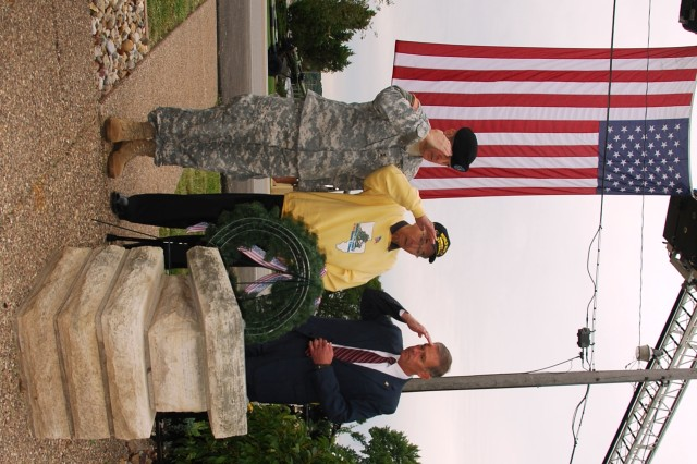 Maj. Gen. Mark MacCarley, Former POW Lyle Sheldon and Joel Himsl, salute the POW/MIA marker after placing a memorial wreath Sept 16.