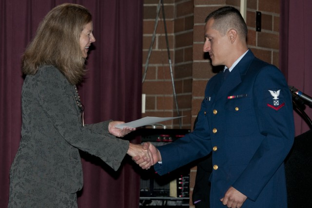 Boatswains Mate Chris Trujillo-Daza, U.S. Coast Guard, receives is Certificate of Citizenship from Anne Corsano, U.S. Citizenship and Immigration Services District Director of the North West, during the Joint Base Lewis-McChord Naturalization Ceremony at McChord Field's Co-Located Club, Sept. 15.
