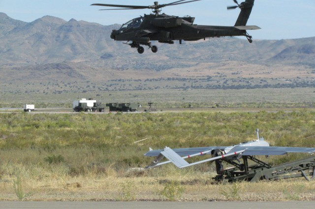 An Apache helicopter takes off at Dugway's Michael Army Airfield as the Shadow unmanned aircraft is readied for its flight onto the battlefield. The two aircraft were involved in a manned-unmanned teaming demonstration known as the Manned Unmanned System Integration Capability exercise.