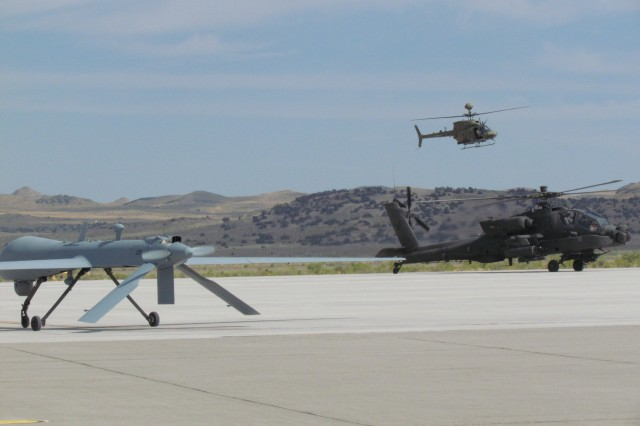 "Following a demonstration flight, Gray Eagle sits on the tarmac as two of its teammates "" Apache and Kiowa "" land at Dugway Proving Ground."