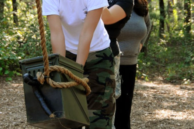 Spouses work to transport supplies across an imaginary minefield during the Leader's Reaction Course.