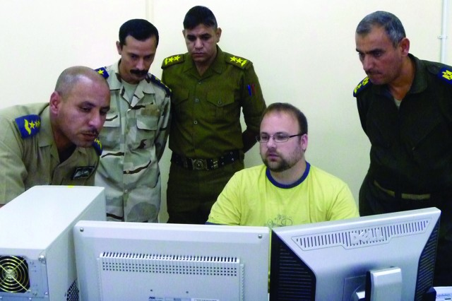 "John Nemeth shows Iraqi officers how to operate instructor and student software for a depot""installed language laboratory.  The officers are with the Iraqi Air Force's English Language Training Program.  Nemeth, an electronics technician at Tobyhanna Army Depot, was part of a depot team that installed two language labs in Iraq."