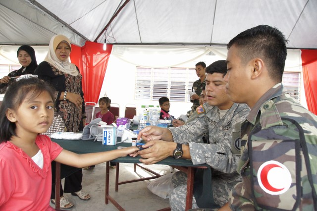 Sgt.  Altamirano Delgado, takes the vital signs of a child from the village of Kampung Orang Asli Solok Terentang, an aboriginal Malaysian village in rural Melaka, Malaysia, September 21, 2011.  Delgado is a Combat Life Saver instructor with the 1984th US Army Reserve Hospital (USARH), 9th Mission Support Command, Ft Shafter, Hawaii.