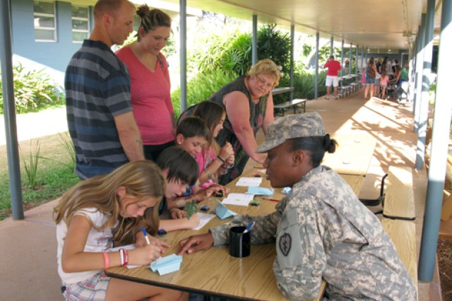 A Soldier with HHBN, 25th ID, assists a student with thumbprint art at Hale Kula Elementary School's book fair, Schofield Barracks, Sept. 16. The book fair had a science and space theme.