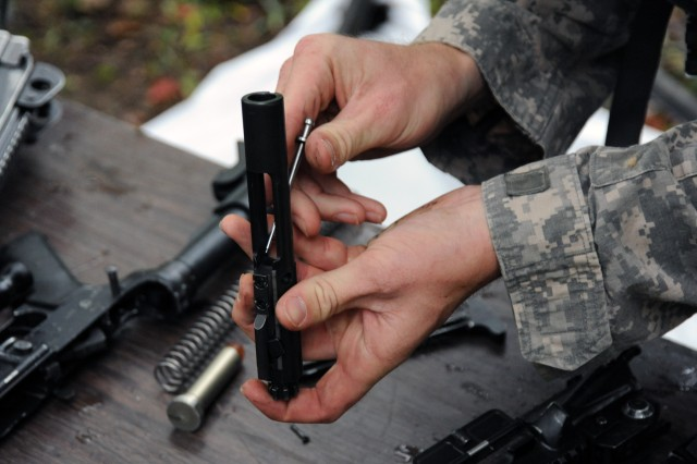 The firing pin to an M-4 rifle is put back into place during a weapons disassembly-reassembly timed event during the 2011 Warfighter Competition at Fort Leonard Wood, Mo., Sept. 18-21, 2011.