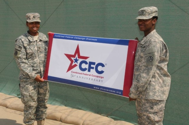 CAMP ARIFJAN, KUWAIT - Capt. Raquel Crisp (left), a native of Oklahoma City, Okla., and Staff Sgt. Sherika Pharr (right) a native of Atlanta, both from Third Army Special Troops Battalion hold a sign that will be displayed for the upcoming Combined Federal Campaign here Oct. 3. CFC marks 50 years of partnership with military forces. Third Army will continue to educate and inspire all servicemembers here to ensure they know that donating to CFC will help those in need. Through nonprofit fundraisers like this, Third Army is building strength between the military service and families in need.