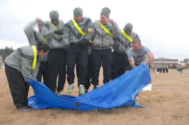 Soldiers assigned to the 80th Ordnance Battalion, 593rd Sustainment Brigade, jump in sync during a team-building exercise in which they had to turn a tarp over whithout any of the members of the team stepping off the tarp as part of the battalion's Junior Leadership Development Day, Sept. 16, 2011, on Joint Base Lewis-McChord, Wash. (Photo by Sgt. Kendra McCurdy) Junior leaders participate in team-building activities