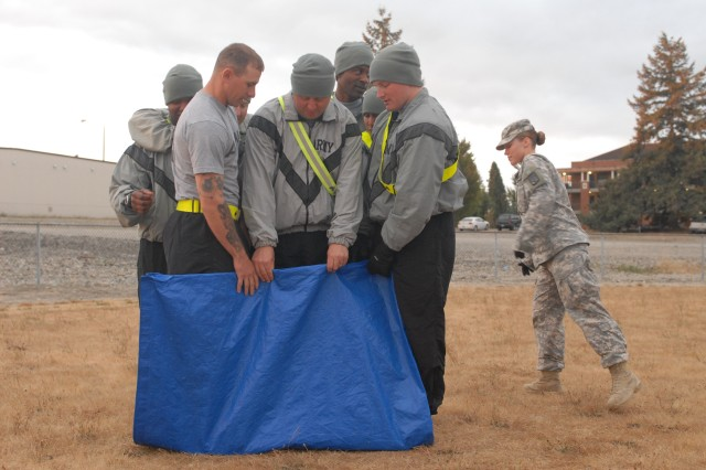 Soldiers assigned to the 80th Ordnance Battalion, 593rd Sustainment Brigade, participate in a team-building exercise in which they had to turn a tarp over whithout any of the members of the team stepping off the tarp as part of the battalion's Junior Leadership Development Day, Sept. 16, 2011, on Joint Base Lewis-McChord, Wash. (Photo by Sgt. Kendra McCurdy)