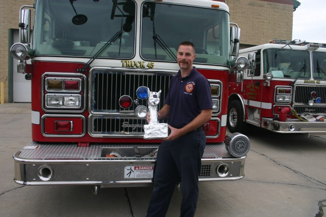 Fort Meade firefighter Christopher Smith holds the department's Trophy of Life presented to him after rescuing a 14-year-old pit bull during a town house fire in Odenton on Sept. 4. Smith found the unconscious pet in a bedroom and carried the dog to safety.