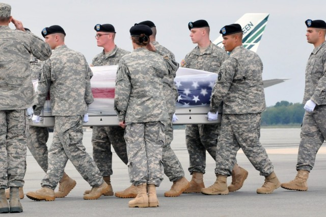 Air Force Col. David E. Pollmiller (left), Commander, Operations Group 436th Airlift Wing, and Brig. Gen. Rhonda Cornum (right), director, Comprehensive Soldier Fitness, render honors to the remains of Sgt. 1st Class Daniel R. Adams, 1st Battalion, 10th Special Forces Group (Airborne), during a dignified transfer conducted by the 3d U.S. Infantry Regiment (The Old Guard) Soldiers, Sept. 15, 2011, at Dover Air Force Base, Del.