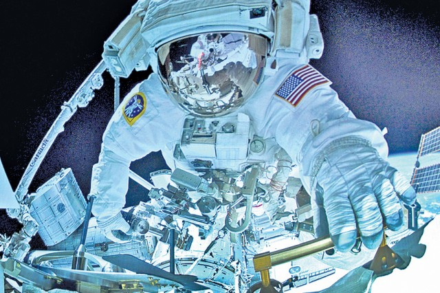 A view of an astronaut during a space walk aboard the International Space Station.