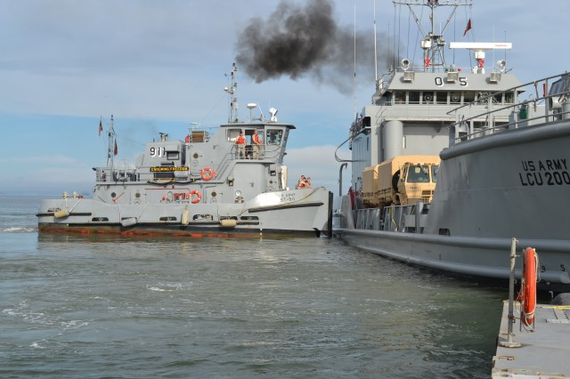 The Small Tug-911, the Enduring Freedom, assigned to the 10th Transportation Battalion, 7th Sustainment Brigade, assists in the docking of the Army Landing Craft Utility-2005 boat at the end of the floating causeway at Fort Story, Va. the evening of Sept. 24 as the brigade kicked off Fall Trident, a Joint Logistics Over The Shore training exercise. A strong tide made docking of the LCU-2005 difficult. Photo by 1st Lt. Andrea Whitaker, 11th Transportation Battalion