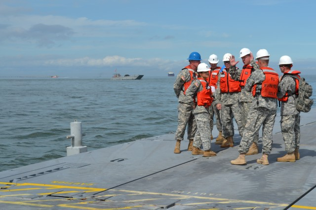 Colonel Stephen Farmen, (right, center) the Army's Chief of Transportation, is briefed by Capt. Kristina Shelton, (left, foreground) 331st Transportation Company (Causeway), 24th Transportation Battalion, on the construction and placement of the trident pier floating causeway during the brigade's annual Joint Logistics Over The Shore training exercise dubbed Fall Trident. This was the first time Col. Farmen witnessed the JLOTS event. He later addressed the group of key leaders about the Army's modernization of equipment, and how the equipment upgrade will result in the Army having an even higher level of well-trained expeditionary force prepared and ready to support any mission, anywhere. Photo by 1st Lt. Andrea Whitaker, 11th Transportation Battalion