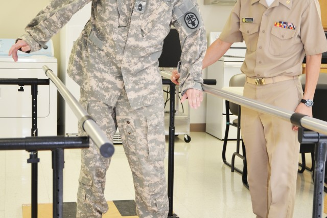 "Master Sgt. David McCurry works on his balance on a rocker board as part of his rehabilitative therapy with Lt. Cmdr. (Dr.) Scott Mitchell, physical therapist and officer-in-charge of the CRDAMC Traumatic Brain Injury Clinic. McCurry, a National Guardsman with the 168th Aviation Brigade from Pendleton, Ore., suffered moderate TBI after being hit by a 107mm rocket blast during his last deployment and said he ""basically had to learn to walk and talk all over again."" (U.S. Army photo by Patricia Deal, CRDAMC Public Affairs)"