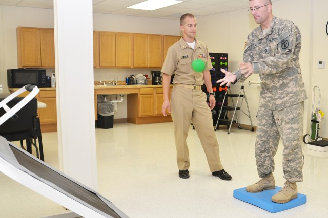 "Master Sgt. David McCurry tosses and catches a ball while standing on a foam board as part of his rehabilitative therapy with Lt. Cmdr. (Dr.) Scott Mitchell, physical therapist and officer-in-charge of the CRDAMC Traumatic Brain Injury Clinic. McCurry, a National Guardsman with the 168th Aviation Brigade from Pendleton, Ore., suffered moderate TBI after being hit by a 107mm rocket blast during his last deployment and said he ""basically had to learn to walk and talk all over again."" (U.S. Army photo by Patricia Deal, CRDAMC Public Affairs)"