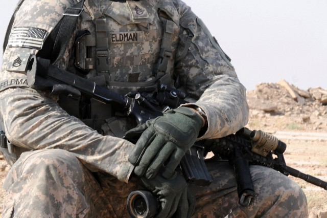 Staff Sgt. Samuel Feldman, a section chief with the 2nd Brigade, 82nd Airborne Division's A Battery, 2nd Battalion, 319th Airborne Field Artillery Regiment, waits with binoculars in hand for an aircraft to fire on its target during an air-ground integration training exercise on a range in Fallujah, Iraq, Sept. 24. During the exercise, forward observers assigned to the 2/82's C Co., 1st Battalion, 325th Airborne Infantry Regiment, and truck drivers from the battalion's Forward Support Company, E Co., 407th Brigade Support Battalion, directed an Apache helicopter to fire on an objective. This training familiarized the drivers with talking to the aircraft in case they have to call for fire to protect themselves on one of their many logistical convoys in the Anbar Province. Feldman is a native of Mount Clemens, Mich.